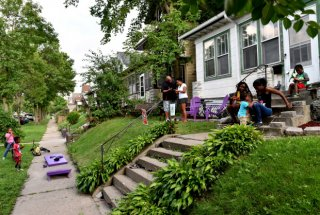 Andrea Giles, center in white, a corrections officer with Ramsey County, hosts her family and neighbors on her recently spruced up front yard in an effort to get people to know their Rondo area neighbors on Wednesday, August 17, 2016. The Knight Foundation provided Giles with a small grant to help her make her front yard more inviting. (Pioneer Press: John Autey)