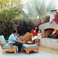 family enjoying outdoor living space with fireplace and lounge chair